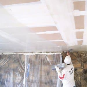 Drywaller smoothing a textured ceiling