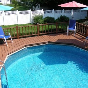 above ground swimming pool enclosed in a deck with chairs and an umbrella