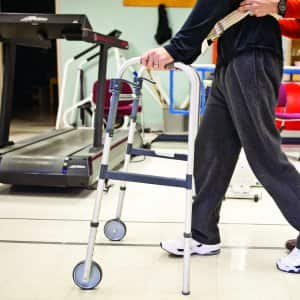 physical therapist working with patient walking
