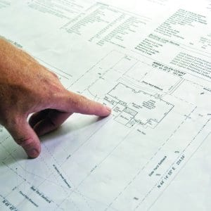 architect examines building blueprints