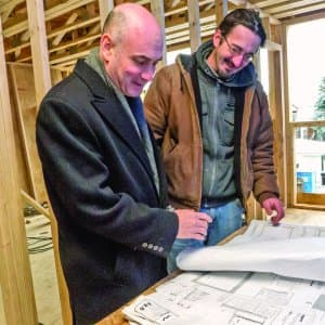 architect examines blueprints for remodeling project