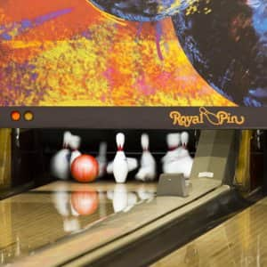 a bowling alley with a ball knocking over some pins