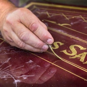 Man's hand applying gold pinstriping on an antique safe from Hall's in Cincinnati, Ohio