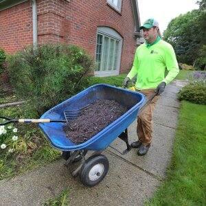 a man hauling a wheelbarrow of mulch