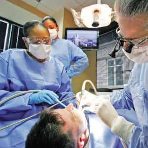 a dentist and hygenist working on a patient's teeth