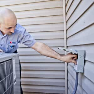HVAC worker inspecting an outdoor A/C unit