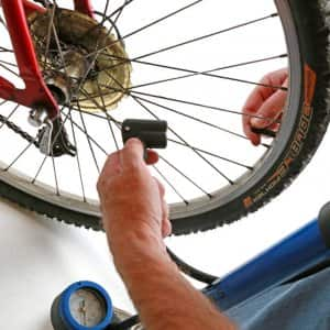 using a pump to inflate a bike tire