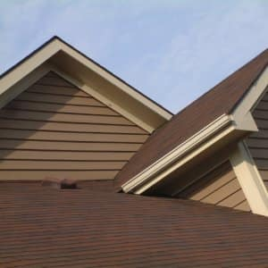 a brown house with tan siding and shingles