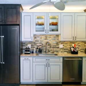 An updated kitchen with white cabinets and tile backsplash