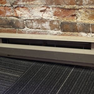 baseboard heater and exposed brick wall
