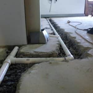 Pipe being installed in basement floor.