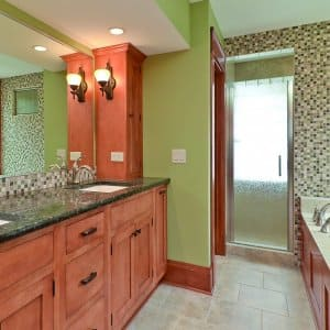 bathroom with green walls wooden cabinets and marble countertops