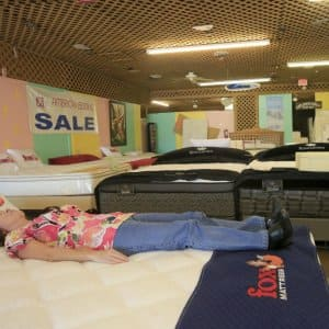 a woman laying on a bed as her friend watches as a mattress shop