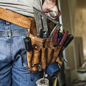 remodeling contractor wearing leather tool belt with utility knife