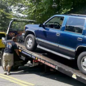 large SUV being hooked onto a tow truck