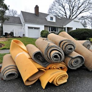 carpet rolls in front of a home