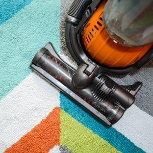 vacuum cleaner on multicolored carpet