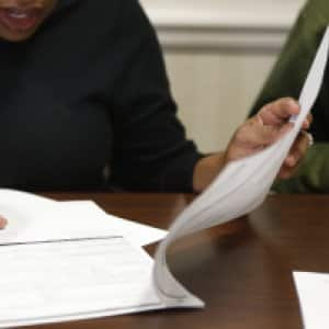 Home buyer signing paperwork at closing. (Photo by Photo by Ray Black III)
