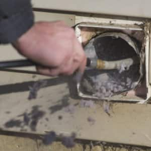 Midwest Air Solutions technician Simon Ashmore performs a dryer vent cleaning at a home in Zionsville, IN.