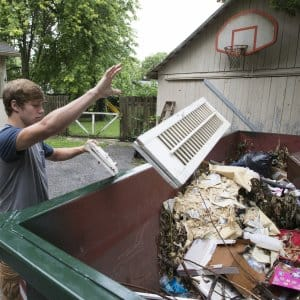 A man tossing junk into a dumpster