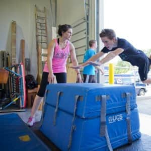 Michelle Hewitt, an assistant instructor at B.A.S.E. Parkour in Fishers, Indiana, helps a student make a leap during a parkour class. (Photo by Eldon Lindsay)