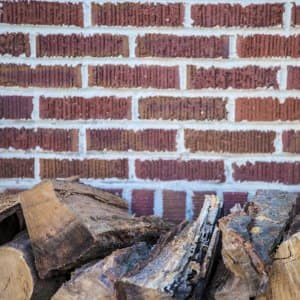 firewood stacked next to a brick wall