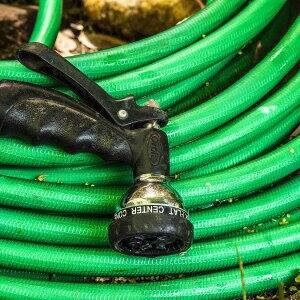 green garden hose and spray nozzle