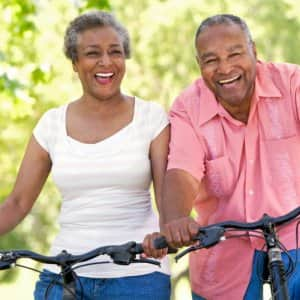 gray haired couple bike riding, seniors bike riding, senior couple bike riding, mature couple bike riding