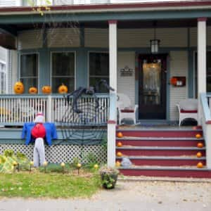 pumpkins, jack-o'-lanterns and a big spider in its web on front porch