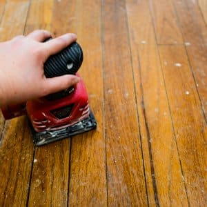 Hand Sander Refinishing A Hardwood Floor