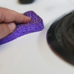 cleaning a stove burner on an oven with a sponge