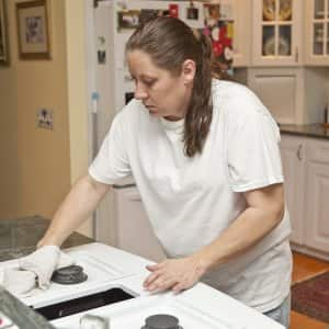 housecleaner cleaning a kitchen stove