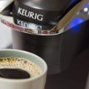A Keurig coffee maker and a cup of coffee
