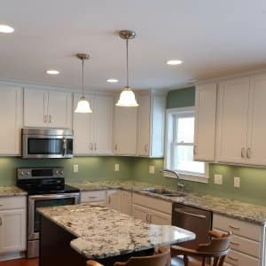 small kitchen with white cabinets, green walls, brown patterned countertops
