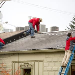 men on roof hanging Christmas lights