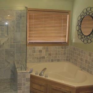The contractors lowered the short wall between the shower and the whirlpool. While updating most of the bathroom, they were able to keep the trim, doors, existing whirlpool and vanity, which cut costs. (Photo courtesy of Angie's List member Mike M., Kansas City, Missouri)