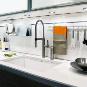 Utensils hanging on a rod over a kitchen counter