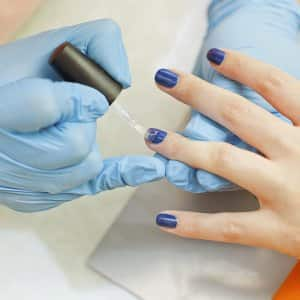 manicurist appying nail polish to a client
