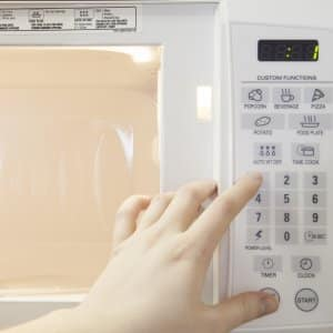 hand pushing buttons on a microwave oven