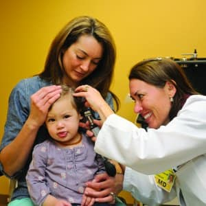 mom holding child during an ear exam