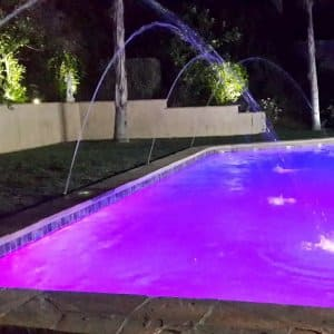 swimming pool with lavendar colored water and water sprinkler.