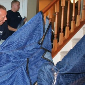 movers protecting stair banister with moving blanket