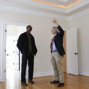real estate agent shows home for sale to buyer