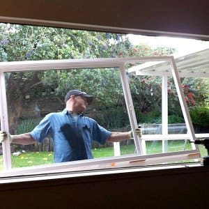 man holding replacement window as he installs it