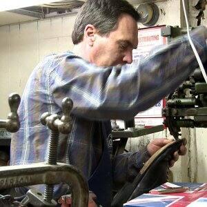 gentleman repairing sole of shoe