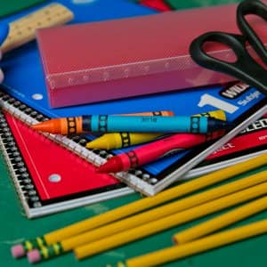 School supplies including glue, pencils, crayons and scissors