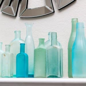 grouping of blue and green sea glass bottles