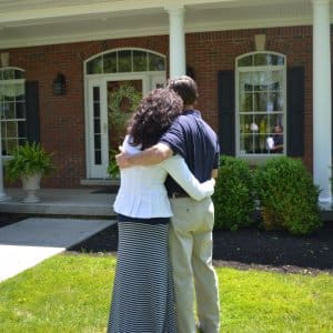 couple hugging in front of home