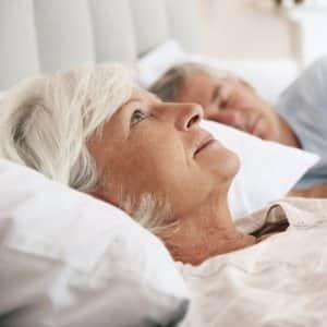 senior woman lying awake in bed