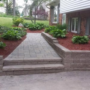 a rock wall and walkway to a brick house